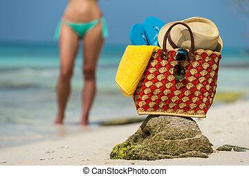 Straw hat, towel beach sun glasses and flip flops on a tropical beach