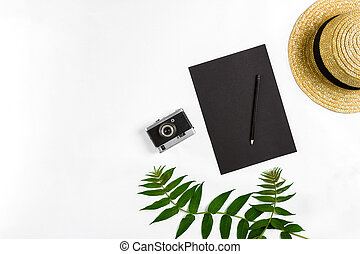 Straw hat with green leaves and old camera on white background, Summer background. Top view