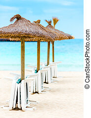 Straw parasols and beds on the sandy beach