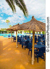 Straw parasols and beds on the sandy beach.