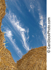 Straw stacks against a blue sky