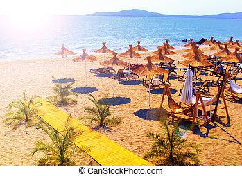 Straw umbrellas on beautiful sunny beach in Bulgaria resort