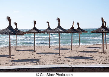 Straw umbrellas on sandy beach.