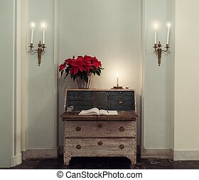 Straw vase with red flower on a chest of drawers in a hall way