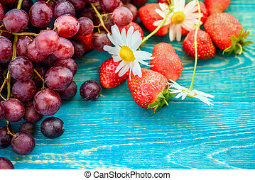 strawberries and grapes on a blue wooden background. Summer backgrounds.