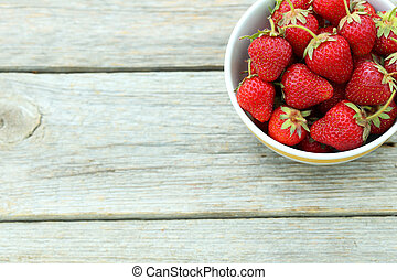 Strawberries berry in bowl on grey wooden background