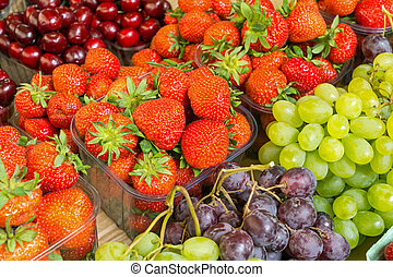 Strawberries, cherries and grapes for sale at a market