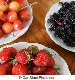 Strawberries, cherries and mulberries on the table