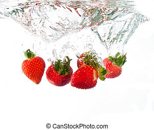Strawberries dropped into water splash