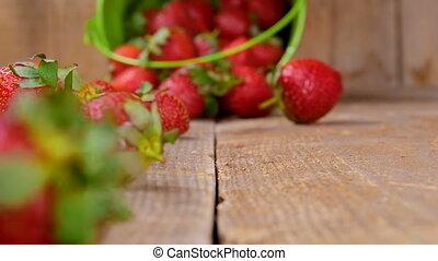 Strawberries falling from bucket on wood - Fresh...