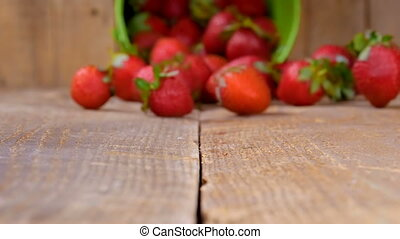 Strawberries falling from bucket on wood in slow motion -...