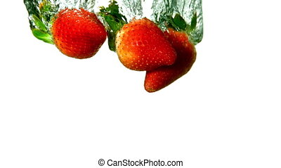 Strawberries falling in water on white background in slow...