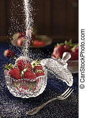 Strawberries in a crystal bowl on a dark blue velvet with a wooden background