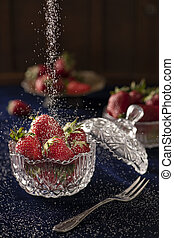 Strawberries in a crystal bowl on a dark blue velvet