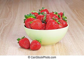 strawberries in a plate on the wooden table