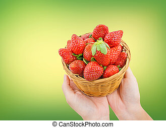 Strawberries in basket on hand