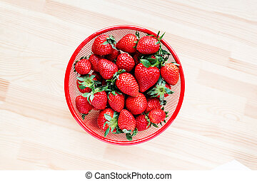Strawberries in red bowl on wooden background.