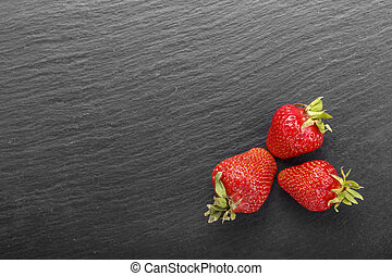 strawberries on a black background place for text