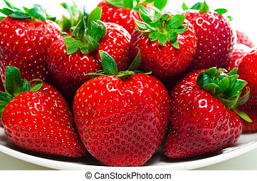 Strawberries on a plate and on the white background