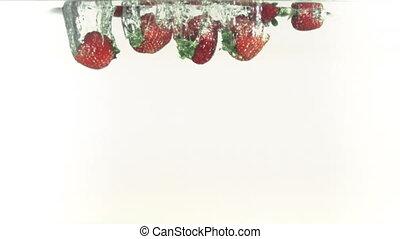 Strawberries splashing into water i