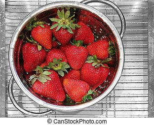 Strawberries - Freshly rinsed strawberries in a stainless...