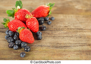 Strawberry and blueberry on wooden background