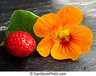 Strawberry and nasturtium flower - ripe, red strawberry with...