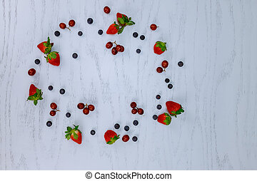 blueberries grapes and strawberries on a white wood