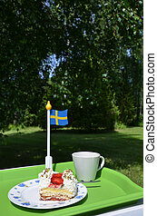 Strawberry cake and a cup on a table with a swedish flag in...