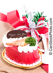 Strawberry cake with bells and ribbon on burlap.