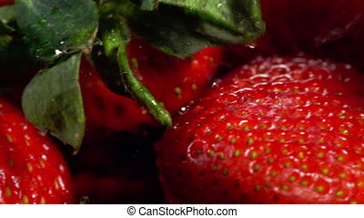 Strawberry close up under drops rain with horizontal motion...