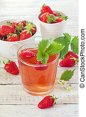 Glass of strawberry compote and strawberries over white wood background