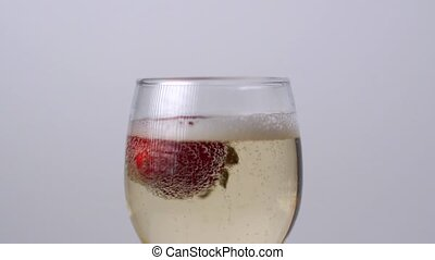 Strawberry falling into a glass of champagne on a white background. Slow motion 1080p