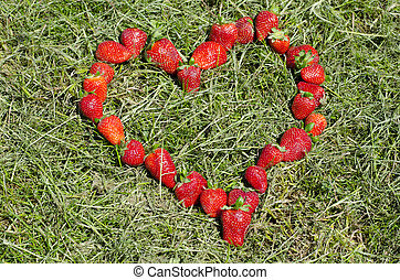 Strawberry heart shape on the green grass