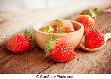 Strawberry in a Bowl on wooden background.