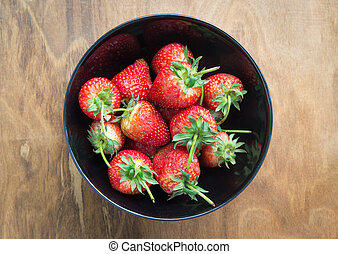 Strawberry in a bowl on wooden table
