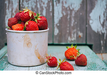 Strawberry in a metal cup on vintage blue background