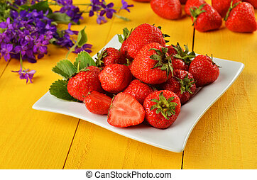 Strawberry in a plate on wooden background