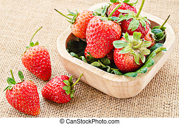 Strawberry in a wooden bowl.