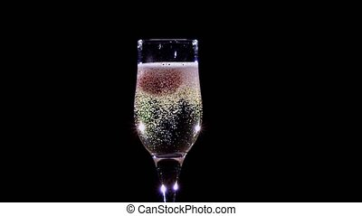 Strawberry in glass with champagne wine covered bubbles. Slow motion