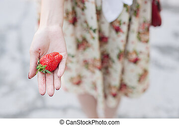 Strawberry in hand woman on the street background.