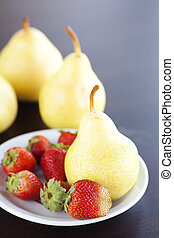 strawberry  in plate and pear on a wooden table