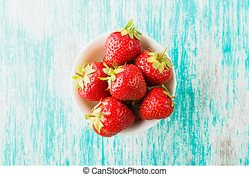 Strawberry in the bowl on the board