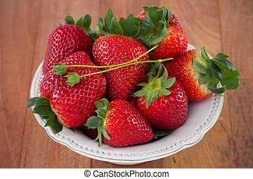 strawberry in white dish on the table