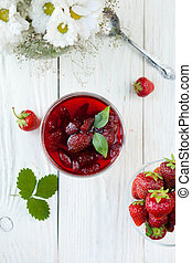strawberry jam in a bowl on a white table, top view