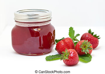 Strawberry jam in a clear jar with fresh fruits on a white...