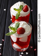 Strawberry jelly with whipped cream, decorated with hearts and fresh mint close up. vertical