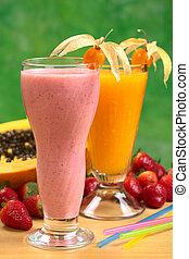 Strawberry milkshake and papaya juice garnished with physalis (Selective Focus, Focus on the physalis on the strawberry milkshake)