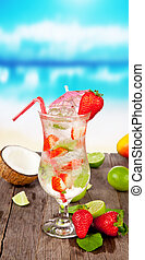 Strawberry mojito with pieces of fruit on wooden table. Blur beach on background