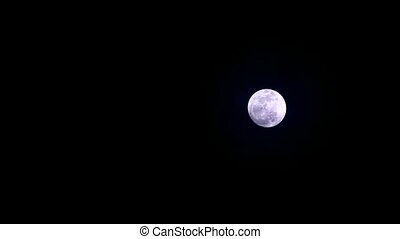 Strawberry moon in the night sky soft and dark cloud moving pass